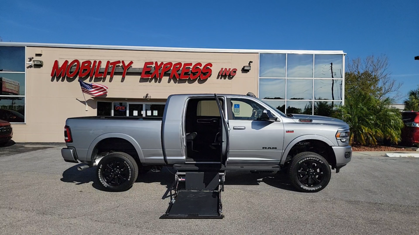 Silver pick up truck with wheelchair lift deployed out of rear passenger door.